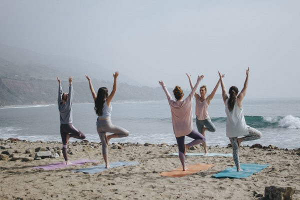 People on a beach doing yoga